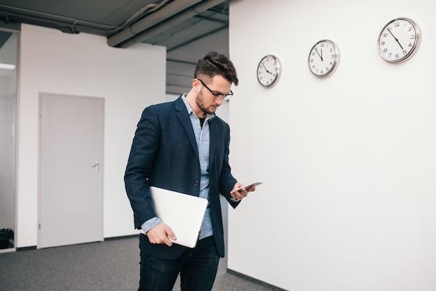 Серьезный парень в очках идет по офису. он носит синюю рубашку, темную куртку, джинсы и бороду. он печатает на телефоне и держит в руке ноутбук.