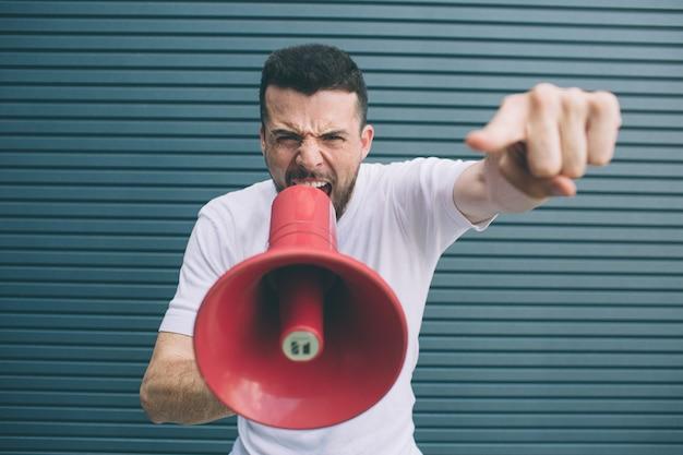 Серьезный парень кричит в мегафон. он держит его одной рукой и указывает на камеру. также парень смотрит на это. изолированные на полосатый Premium Фотографии
