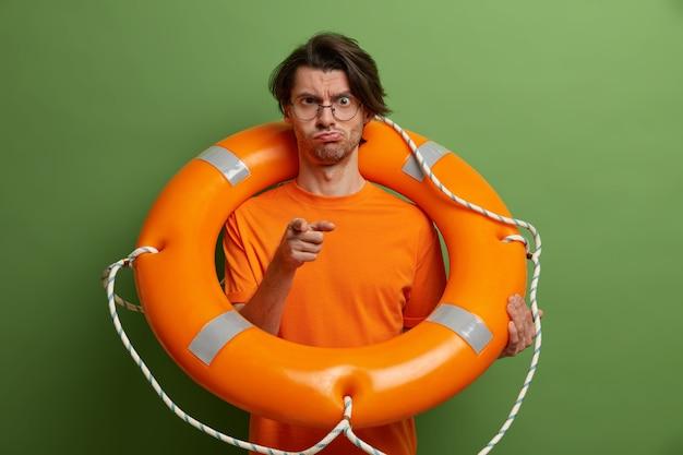 真面目な男があなたを指さし、膨脹可能な救命浮輪でポーズをとり、事故防止に気を配り、顔を笑い、オレンジ色の服を着ます