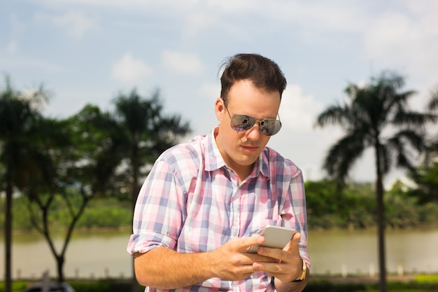 Serious guy texting sms on smartphone while walking outdoors