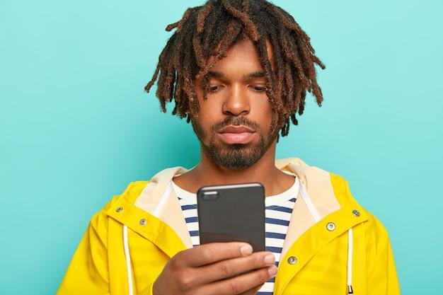 진지한 남자는 현대적인 휴대 전화를 사용하고, 인터넷 웹 페이지를 서핑하고, 온라인 결제를하고, 줄무늬 점퍼와 방수 노란색 비옷을 입습니다.