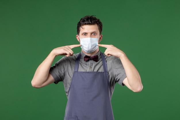 Cameriere serio in uniforme con maschera medica e indicandosi su sfondo verde