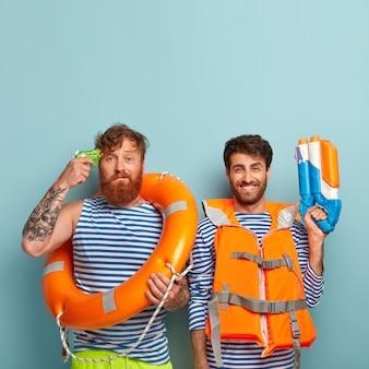 Ragazzi seri in posa in spiaggia con giubbotto di salvataggio e salvagente