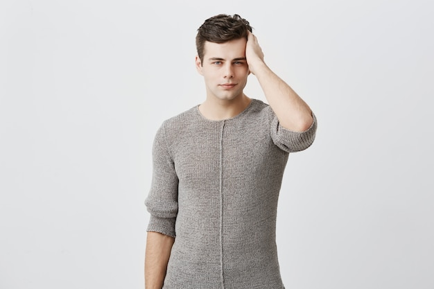 Serious handsome attractive man with dark hair and appealing blue eyes, has stylish hairdo, looks confidently, touching his hair. muscular fit dressed casually male model posing against gray wall