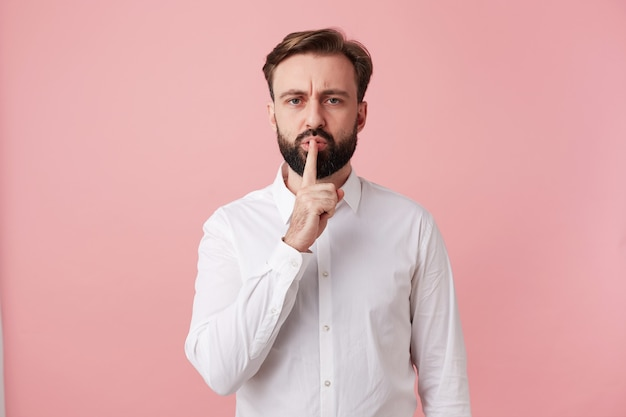 Serious handsome bearded brunette guy with trendy hairstyle holding forefinger on his mouth and frowning eyebrows, asking to keep silence while posing over pink wall