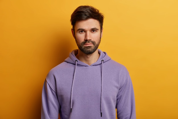 Serious handsome bearded european guy looks directly , has thick bristle, wears purple hoodie, dressed in casual hoodie, poses over yellow wall, listens information carefully.