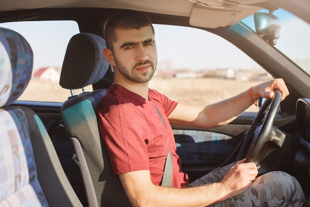 Serious handsome bearded male driver poses in his car, rides auto, uses safety belt, being experienced