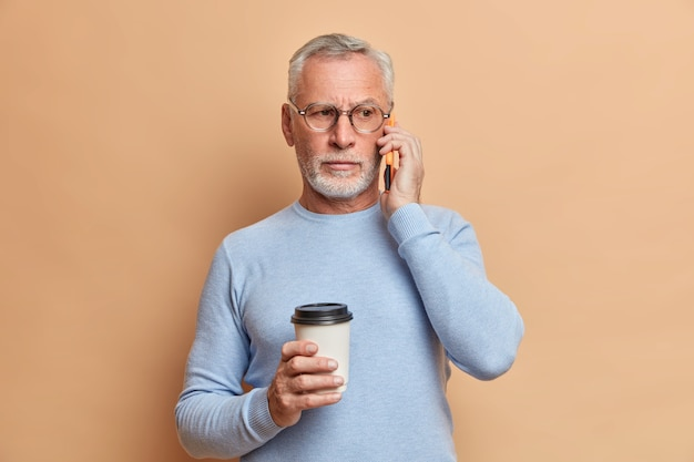 真面目なハンサムなひげを生やした男は電話で会話をし、スマートフォンを耳の近くに保ち、コーヒーブレイクを楽しんでいます。