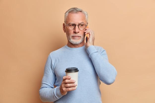 Uomo barbuto bello serio ha una conversazione telefonica tiene lo smartphone vicino all'orecchio gode di pausa caffè distoglie lo sguardo indossa occhiali trasparenti e ponticello isolato sopra il muro marrone