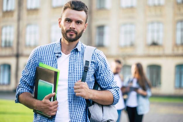 大学の建物でバックパックと本を手にカジュアルな服を着た真面目なハンサムなひげを生やした学生の男