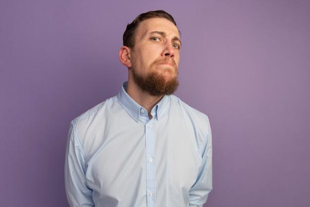 L'uomo biondo bello serio esamina la parte anteriore isolata sulla parete viola
