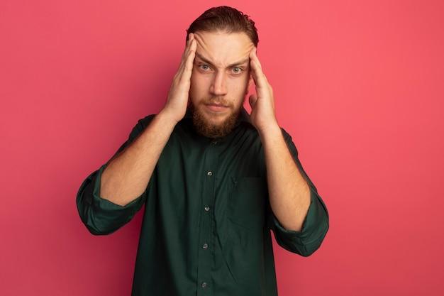Uomo biondo bello serio mette le mani sulle tempie isolate sulla parete rosa