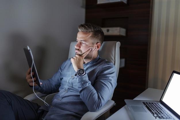 Серьезный красивый кавказский бородатый бизнесмен используя таблетку для работы. в ушах наушники, на столе ноутбук. концепция работы поздно ночью.