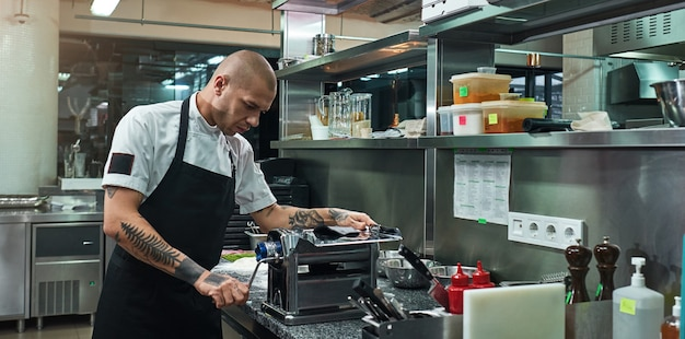Serious and handsome chef with tattoos on his hands rolling a black dough through pasta machine