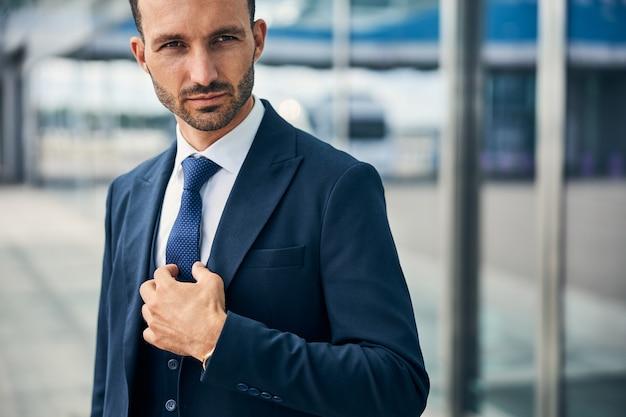 積極的な方法で横を向いてネクタイを固定する真面目なハンサムな男
