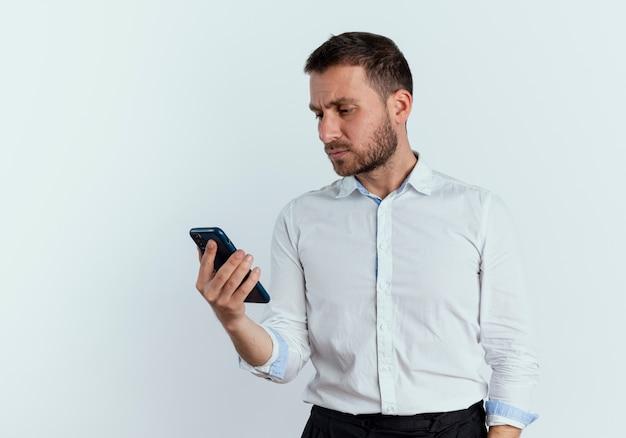 L'uomo bello serio tiene ed esamina il telefono isolato sulla parete bianca