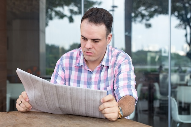 Serious handsome man reading newspaper