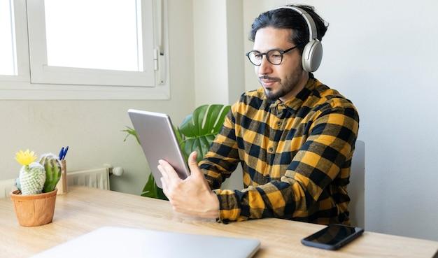 テーブルに座っている真面目なハンサムな男は、ヘッドフォン付きのタブレットを使用しています