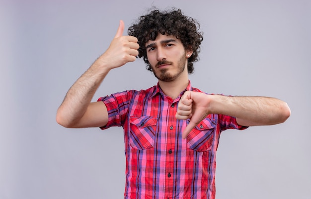 A serious handsome man with curly hair in checked shirt showing thumbs up and down