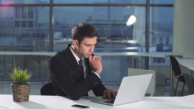 モニター画面で探しているラップトップを使用して作業して深刻なハンサムな男