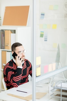 Serious handsome marketing expert talking to customer on phone