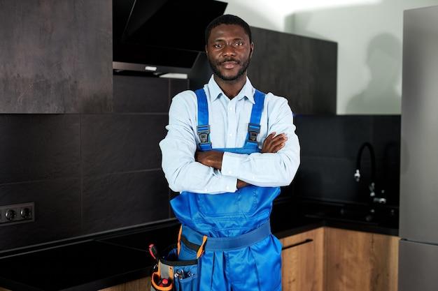 青い制服を着た深刻なハンサムな若いアフリカの便利屋配管工。カメラを見てポーズをとってキッチンで全体的に家に立っている若い熟練した便利屋。修理工サービス、ハードワークコンセプト