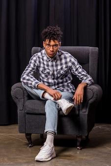 カメラ目線の肘掛け椅子に座っている深刻なハンサムな若いアフリカ人