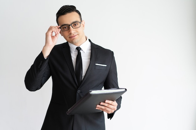 Serious handsome young businessman adjusting glasses and holding folder.