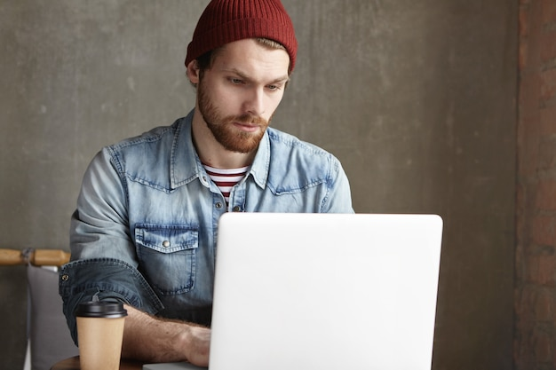 ラップトップコンピューターでリモートで作業する流行の服に身を包んだ深刻なハンサムな若いヨーロッパのフリーランサー、心配そうな顔つき、締め切りのストレスを回避するために時間内に彼の仕事を終わらせようとしている