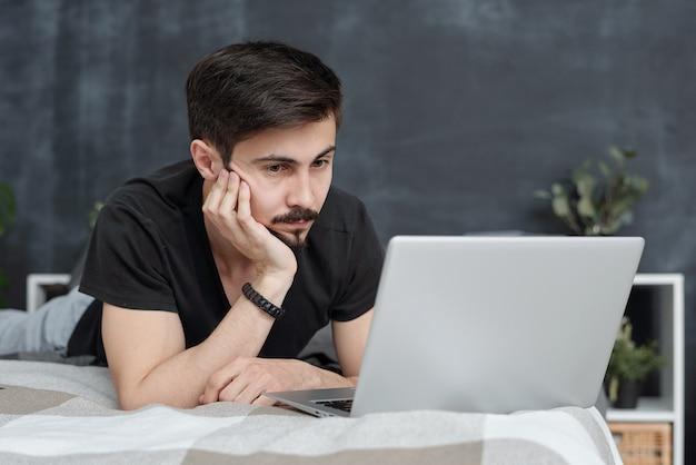 침대에 누워서 자기 격리에서 온라인으로 영화를 보는 동안 손에 기대어 심각한 잘 생긴 젊은 남자