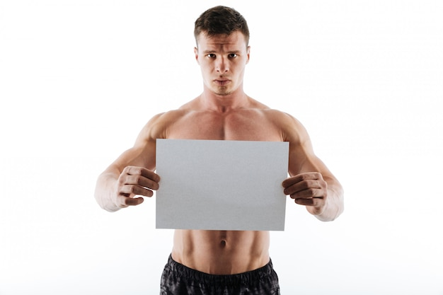 Serious handsome young sportsman holding copyspace paper