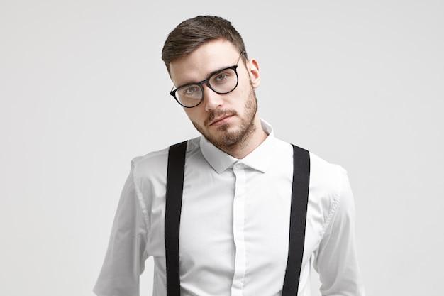 あなたの情報のためのコピースペースで白いスタジオの壁の背景に対して隔離されたポーズでサスペンダーとトレンディな眼鏡と白いフォーマルシャツを着ている深刻なハンサムな若い無精ひげを生やした男性従業員
