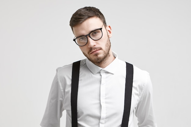 Dipendente maschio serio bello giovane con la barba lunga che indossa occhiali alla moda e camicia bianca formale con bretelle in posa isolato su sfondo bianco muro studio con copyspace per vostra informazione