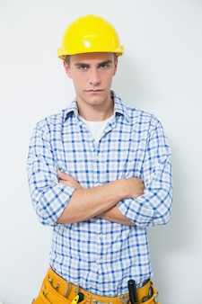 Serious handyman in yellow hard hat with arms crossed