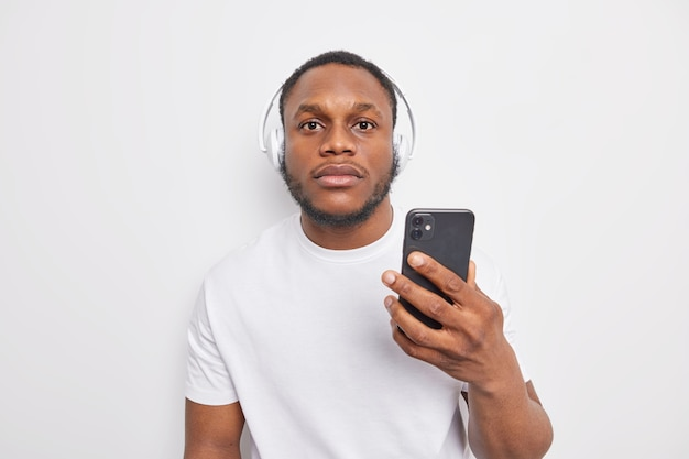 Serious hipster guy with dark skin holds mobile phone and listens to  to music via headphones