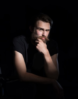 椅子に座っている深刻な流行に敏感な男。黒の背景に分離