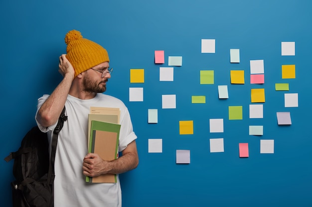 Serious hipster rubs head, looks seriously at colorful notes stuck on wall, recalls necessary information
