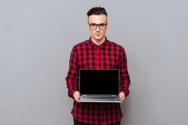 Серьезный хипстер, показывающий пустой экран ноутбука