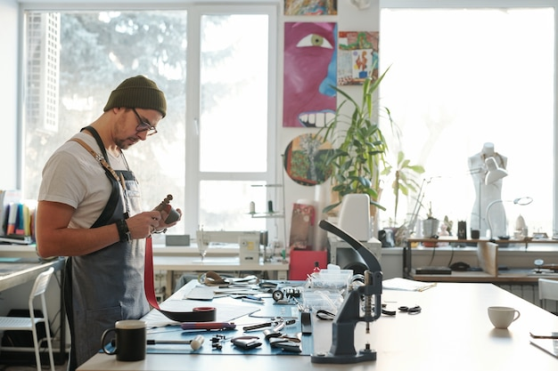 Serious hipster young man in glasses burnishing edge of leather belt while working in own creative workshop