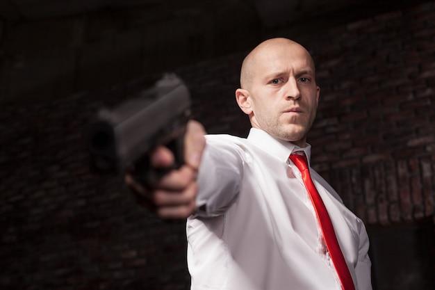赤いネクタイの深刻な雇われ殺人者は銃を狙います。プロの秘密エージェントのコンセプトです。