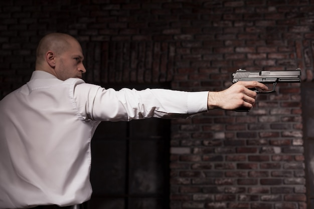 빨간 넥타이에 심각한 고용 된 살인자가 총을 목표로