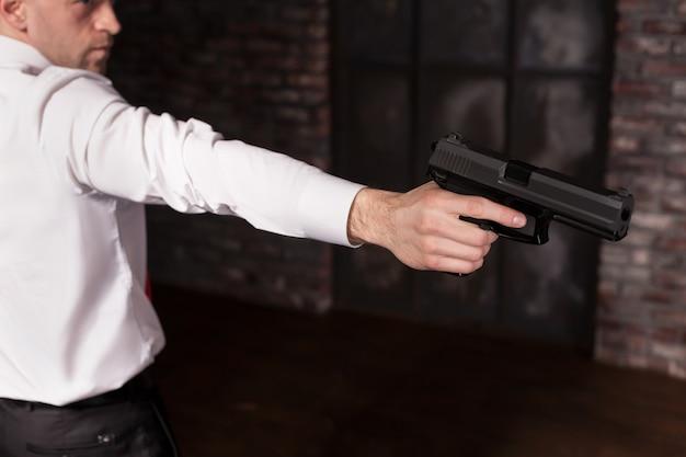赤いネクタイの深刻な雇われ殺人者は銃を目指しています