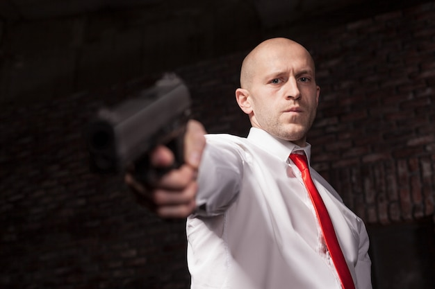 Serious hired murderer in red tie aims a gun. professional secret agent concept.