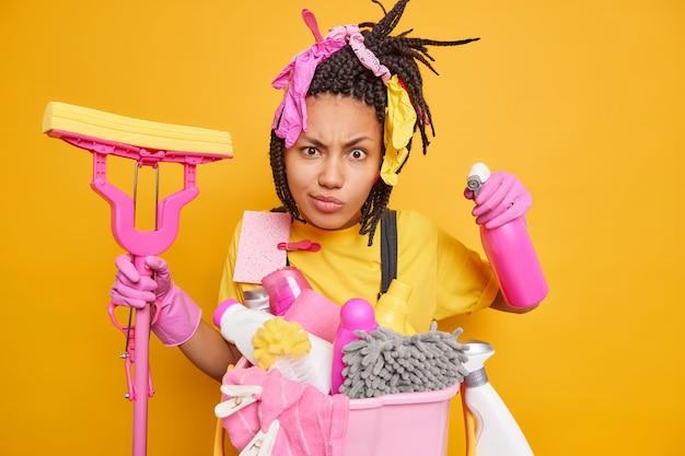 Серьезная домработница с дредами держит химическое моющее средство и швабру