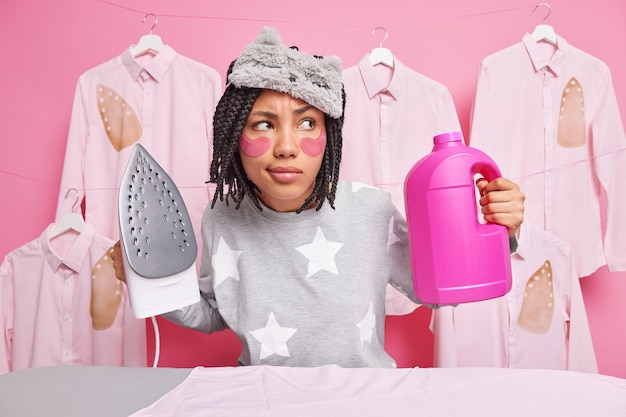 思いやりのある表情に集中した真面目な主婦が自宅で洗濯やアイロンをかけ、室内でアイロンをかけた服に囲まれて家事をしている