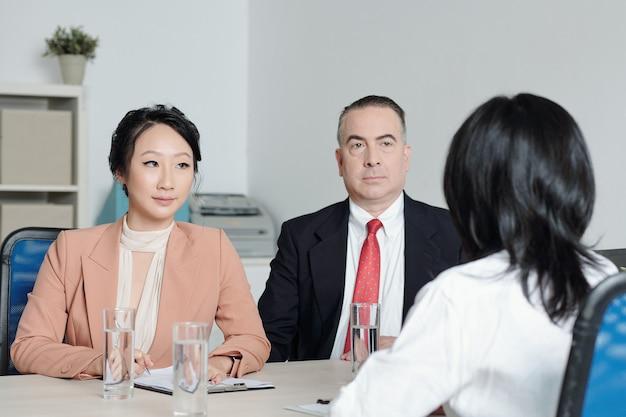 진지한 인사 관리자와 회사 ceo가 면접에서 지원자와 이야기하고 있습니다.