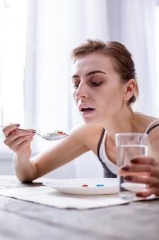 Серьезная болезнь. подавленная молодая женщина принимает таблетки во время тяжелого заболевания