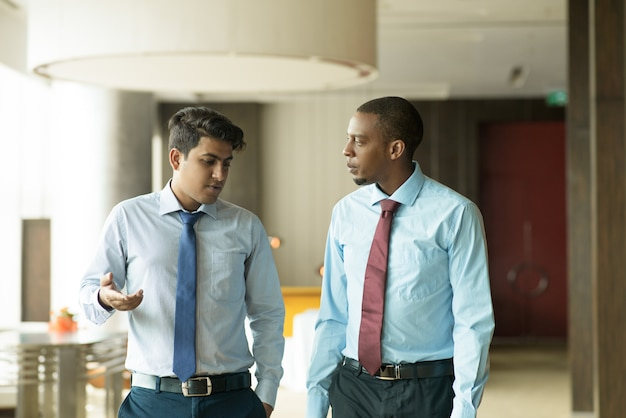 Serious indian businessman sharing his problems with coworker