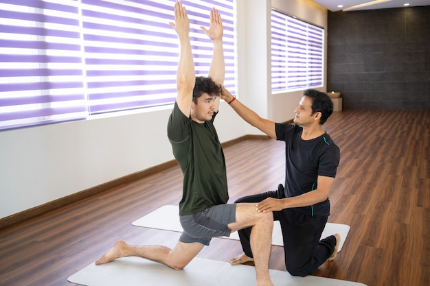 Serious indian instructor helping beginner at yoga class