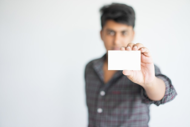 Serious indian man in casual wear showing empty card.